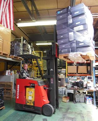 President and founder Robert Toporek moves a pallet of computers, making room for 90 more Dell Pentium 4 desktops